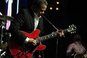 Eddie Martinez photo playing an ES-335 guitar.